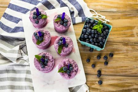 paletas de hielo: Paletas de helado de ar�ndanos hechas en casa hechas en vasos de pl�stico.