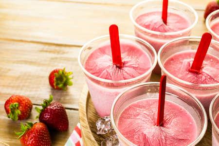 helados con palito: Paletas de helado de fresa caseras hechas en vasos de pl�stico. Foto de archivo