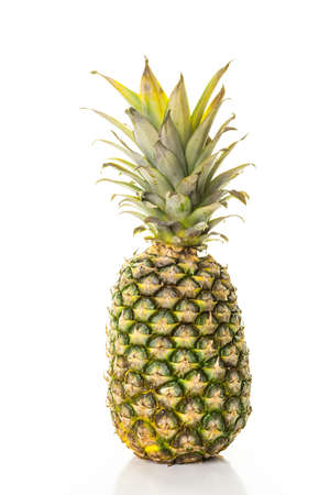 Fresh organic pineapple on a white wood board.