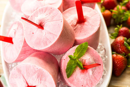 Homemade strawberry popsicles made in plastic cups.