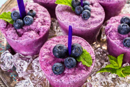 popsicles: Homemade blueberry popsicles made in plastic cups.