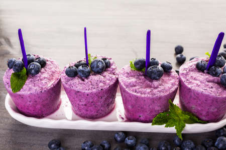 Homemade blueberry popsicles made in plastic cups.