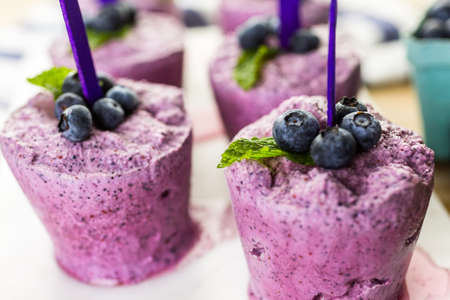 paletas de hielo: Homemade blueberry popsicles made in plastic cups.