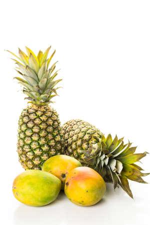 Verse biologische mango en ananas op een witte houten bord. Stockfoto
