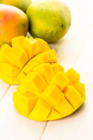 Fresh organic mango on a white wood board.