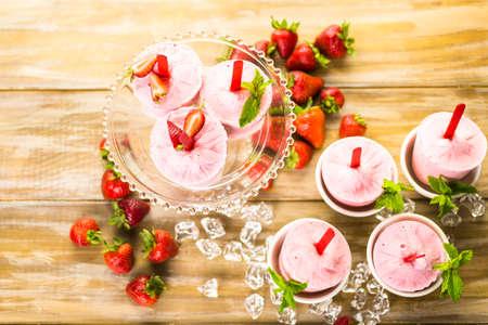 paletas de hielo: Paletas de helado de fresa caseras hechas en vasos de pl�stico. Foto de archivo