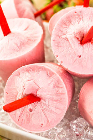 popsicles: Homemade strawberry popsicles made in plastic cups.