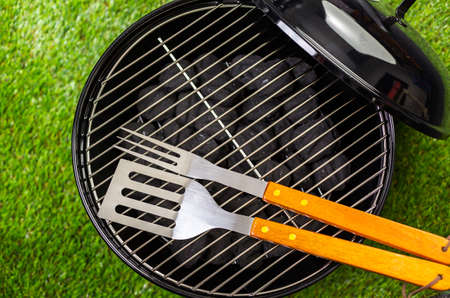 barbie: Small round charcoal grill ready for grilling at the summer picnic.