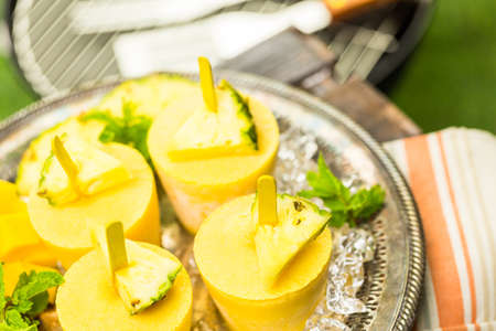 Homemade low calorie popsicles made with mando, pineapple and cocconut milk at the summe rpicnic. Imagens - 42020816