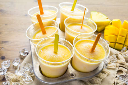 Homemade low calorie icepops made with mango, pineapple and coconut milk. Imagens - 42021698
