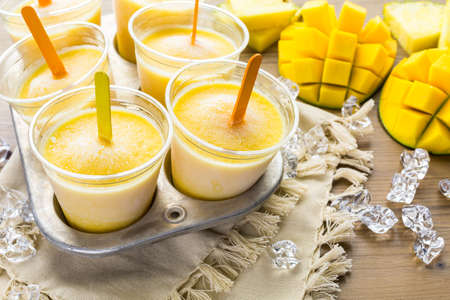 Homemade low calorie icepops made with mango, pineapple and coconut milk.
