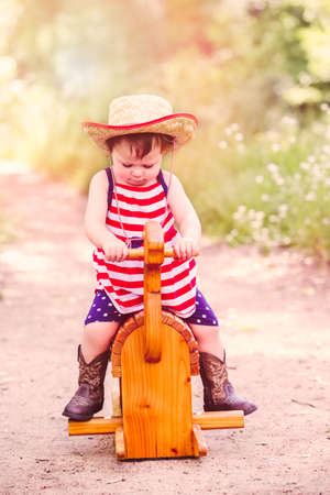 accessories horse: Toddlers having fun in the park for July Fourth. Stock Photo