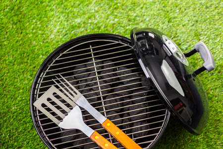 Small round charcoal grill ready for grilling at the summer picnic.