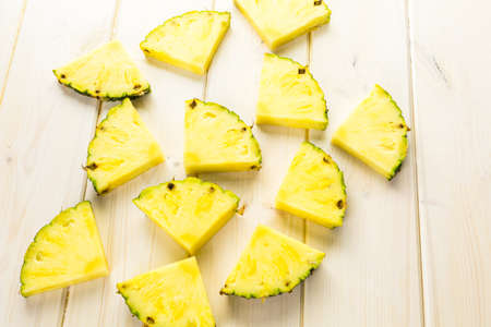 Slices of organic pineapple on a white board.