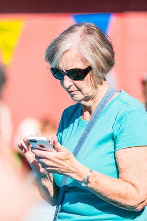 Denver, Colorado, USA-July 11, 2015. Grandmoter using smart phone for texting.
