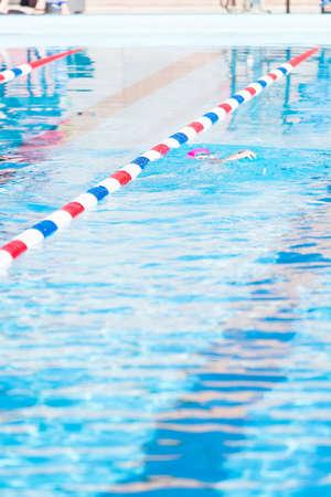 Kinderen zwemmen in de zomer in het buitenzwembad.