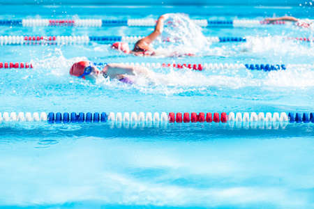 Kinderen zwemmen ontmoeten in het buitenzwembad in de zomer.