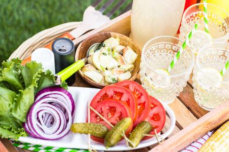 在公园里野餐,吃着柠檬水和汉堡。