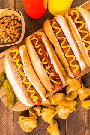 calor: Perros calientes a la parrilla en un perro caliente blanco bollos con la mostaza y la salsa de tomate.