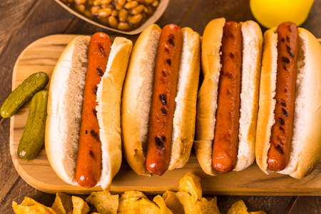 long bean: Grilled hot dogs on a white hot dog buns with chips and baked beans on the side. Stock Photo