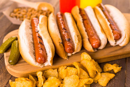 Grilled hot dogs on a white hot dog buns with chips and baked beans on the side. Imagens