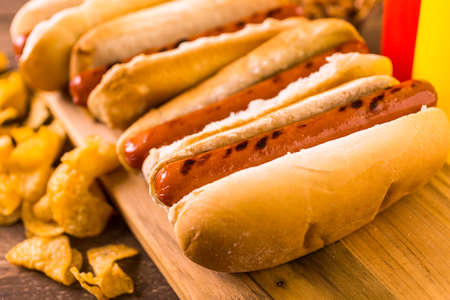 hotdog: Grilled hot dogs on a white hot dog buns with chips and baked beans on the side. Stock Photo