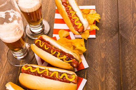 hot beverage: Grilled hot dogs with mustard and ketchup on the table with draft beer.