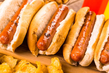 Grilled hot dogs on a white hot dog buns with chips and baked beans on the side. Stock Photo