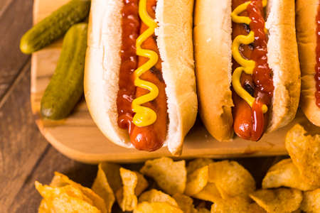 salty: Grilled hot dogs on a white hot dog buns with mustard and ketchup.