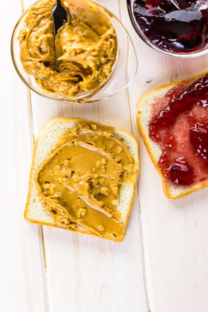 pb: Homemade peanut butter and jelly sandwich on white bread.