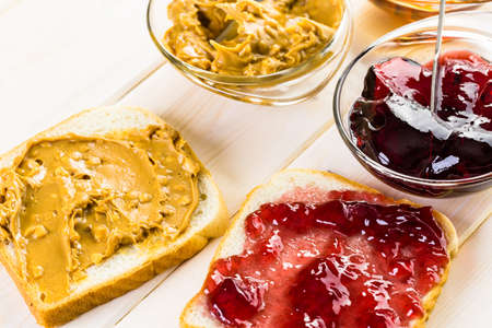 peanut butter and jelly: Homemade peanut butter and jelly sandwich on white bread.