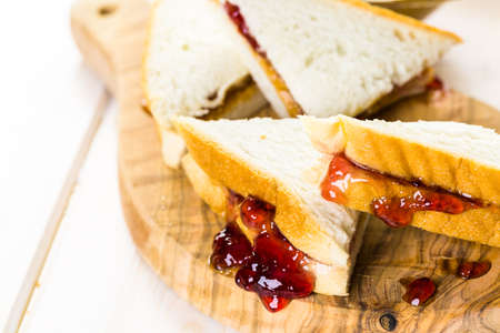 Homemade peanut butter and jelly sandwich on white bread.