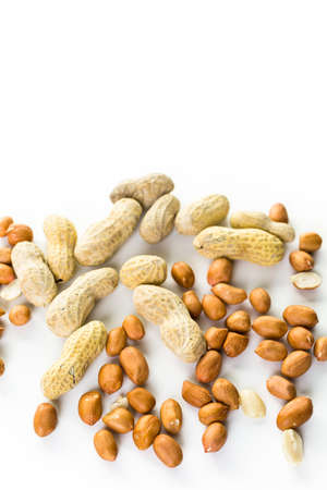 indulgence: Peanuts peeled and in shells on a white background. Stock Photo
