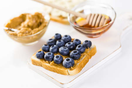fryed: Homemade peanut butter and blueberry sandwich on white bread. Stock Photo