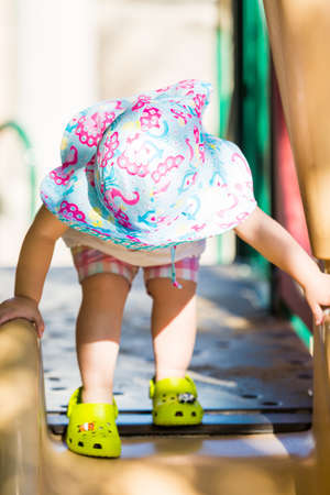 play the old park: Little girl playing outside on toddlers playground. Stock Photo