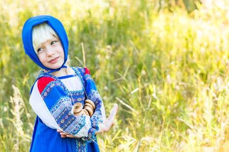 russian ethnicity caucasian: Russian children in traditional Russian costumes playing in the forest.