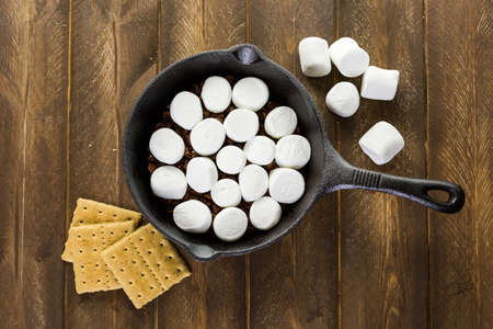 chocolate chips cookies: Preparing smores dip prepared with large marshmallows in cast iron pan.