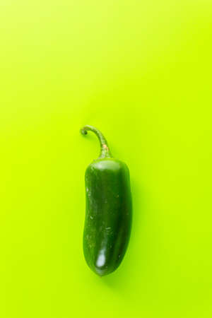 Jalapeno pepper on green background.