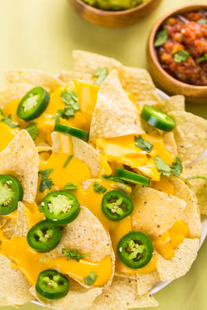 Vegetarian nachos with tortilla chips and fresh jalapeno peppers.