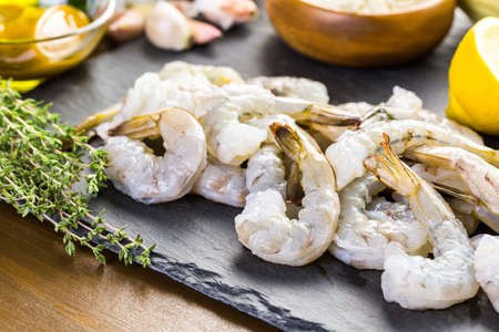 Raw peeled shrimp with tails with lemon on sutting board.
