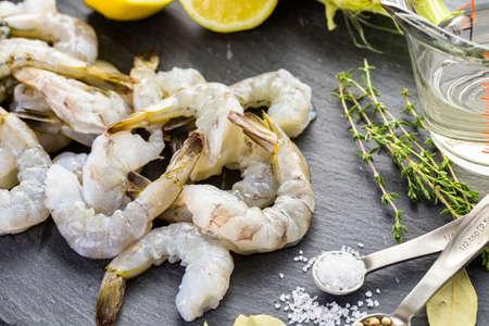 jumbo shrimp: Raw peeled shrimp with tails with lemon on sutting board.