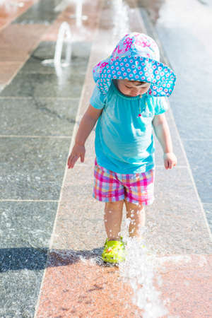 denver parks: Cute toddler girl playing with small fountains in splash park.
