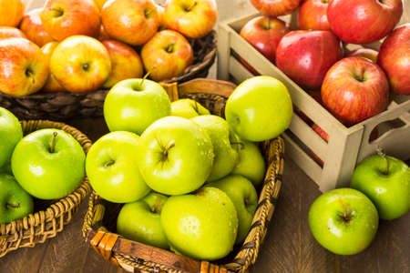 Variety of organic apples in baskets on wood table. Banco de Imagens