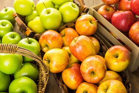 green apples: Variety of organic apples in baskets on wood table. Stock Photo
