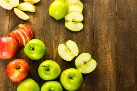 variety: Variety of organic apples sliced on wood table.