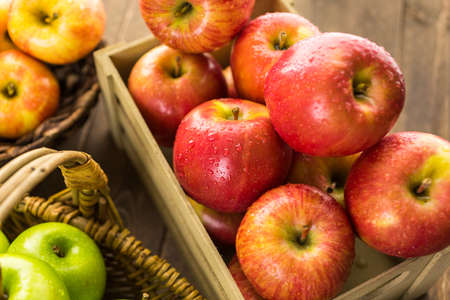 Variety of organic apples in baskets on wood table. Stock Photo