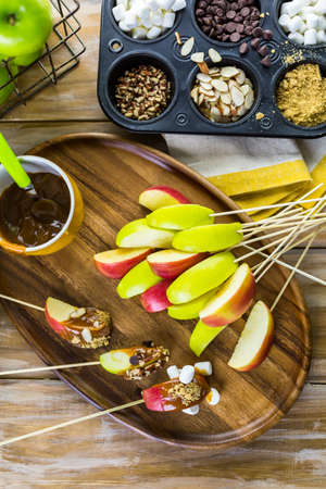 toppings: Apple slices dipped in caramel and covered with different toppings.