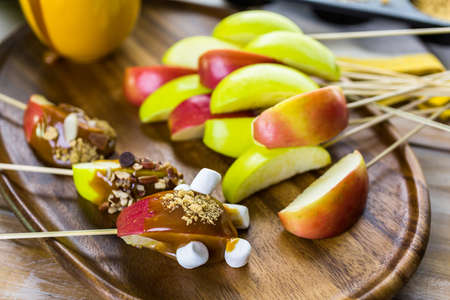 Apple slices dipped in caramel and covered with different toppings.