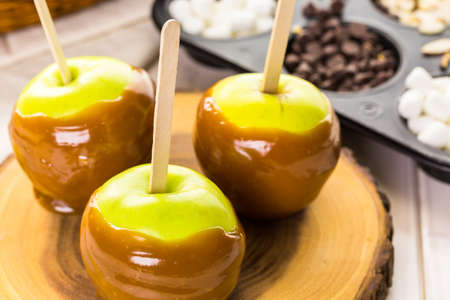 taffy apple: Apples freshly dipped in caramel on cutting board.