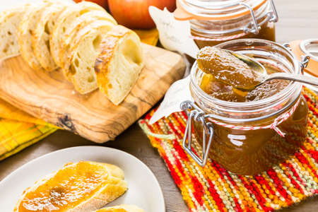 Homemade apple butter and freshly baked bread on the table. Imagens - 45344397